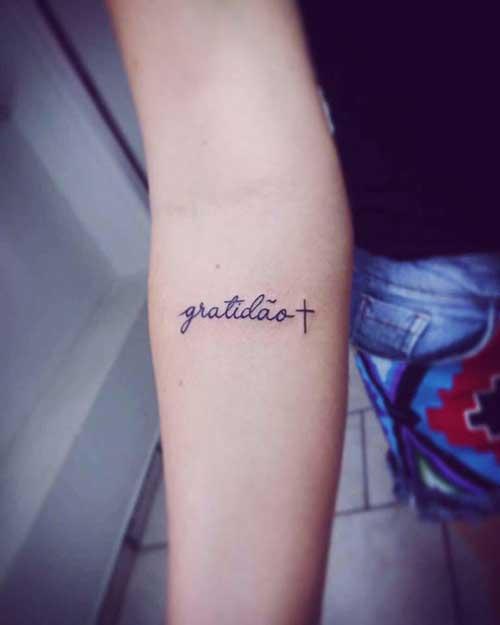 tatuagem gratidão no braço com cruz