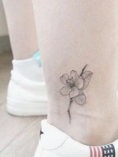 tatuagem de flor no tornozelo