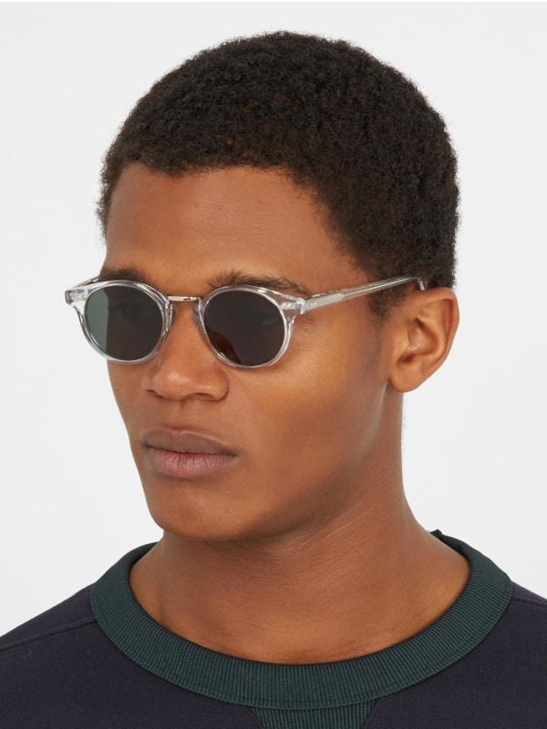 homem com óculos de sol redondo e transparente