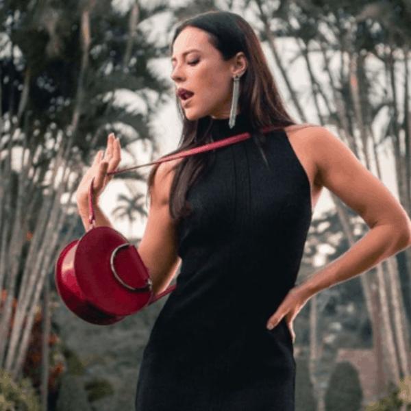 Paolla Oliveira com bolsa redonda de couro vermelha