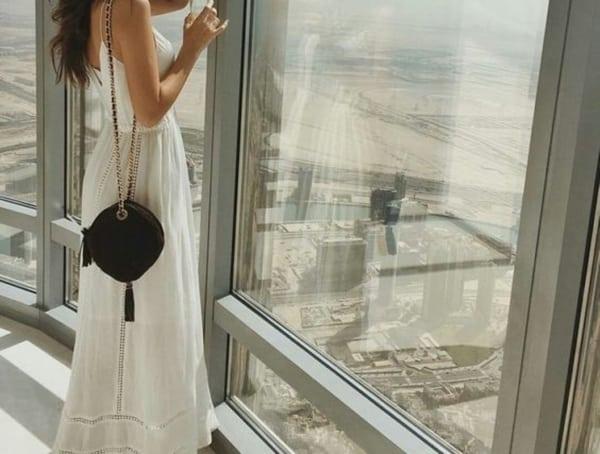 Vestido branco com bolsa redonda preta