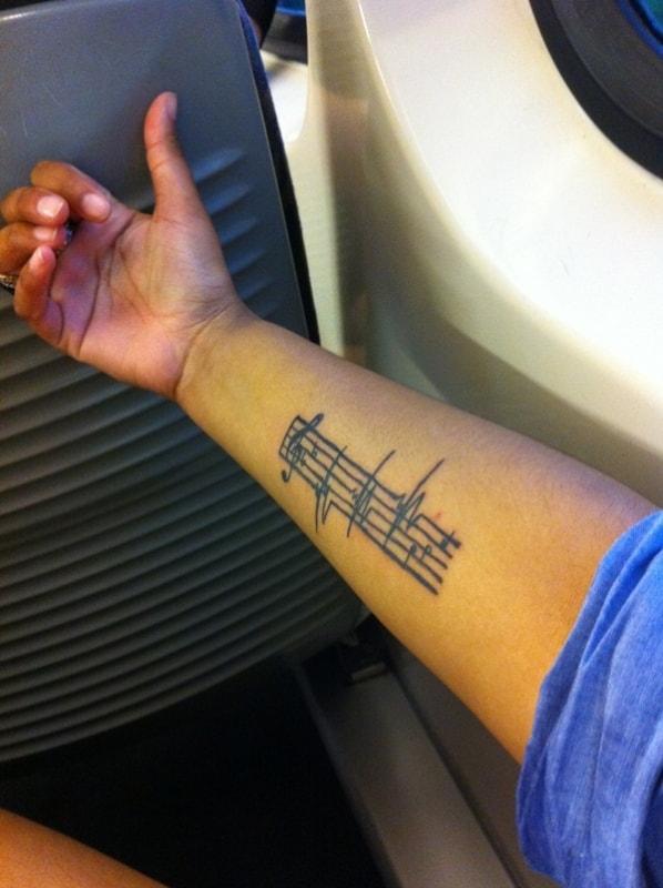ideia de tatuagem de música no braço