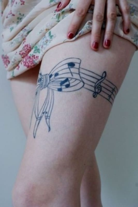 tatuagem de símbolo de música delicada