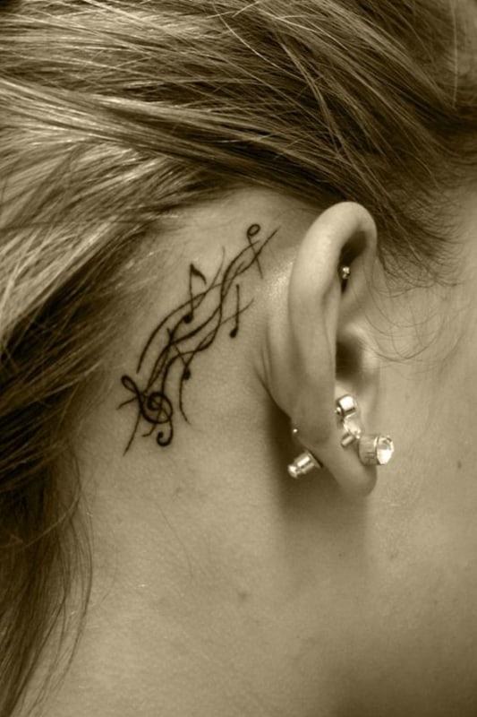 tatuagem de símbolo de música no pescoço