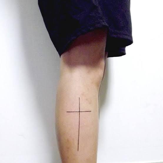 tatuagem na panturrilha masculina cruz minimalista