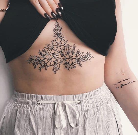 tatuagem preta e branca entre os seios