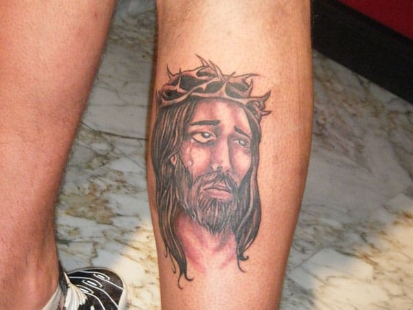 rosto de Jesus tatuado na perna