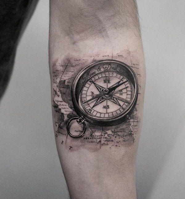 tattoo de bussola desenhada no biceps masculino