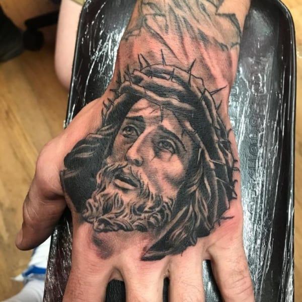 tatuagem grande de Jesus na mão