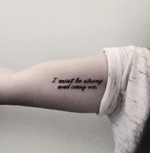 tatuagem no bíceps feminina com frase escrita