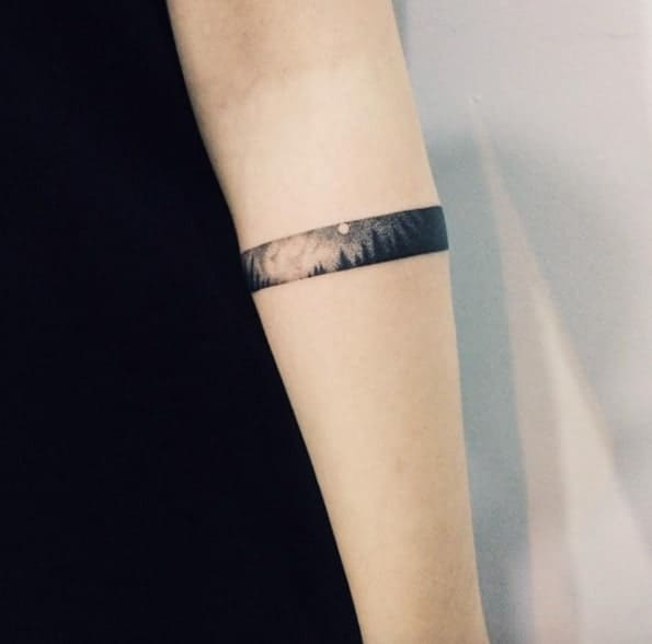 tatuagem no bíceps masculino bracelete com cenario
