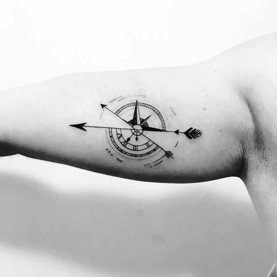 tatuagem no bíceps masculino bussola minimalista