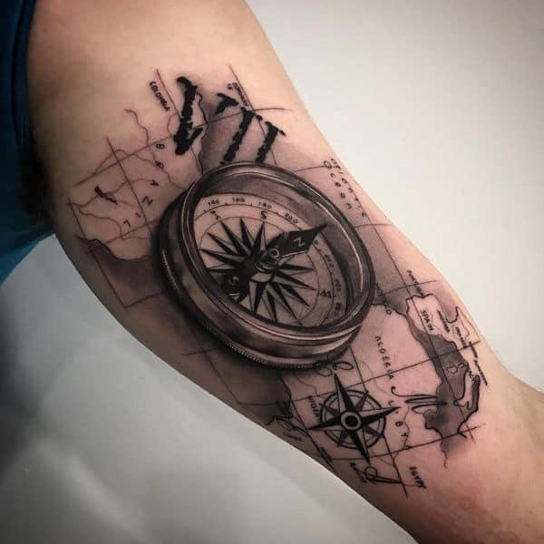 tatuagem no bíceps masculino bussola sombreada