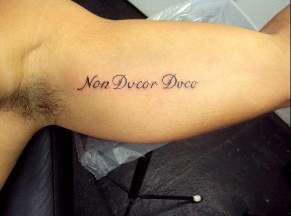 tatuagem no bíceps masculino escrita em latim
