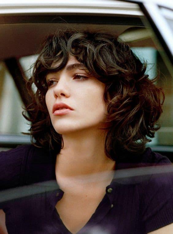 cabelo feminino ondulado com corte em camadas e franja