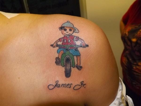 Tatuagem de bonequinhos com nome no ombro