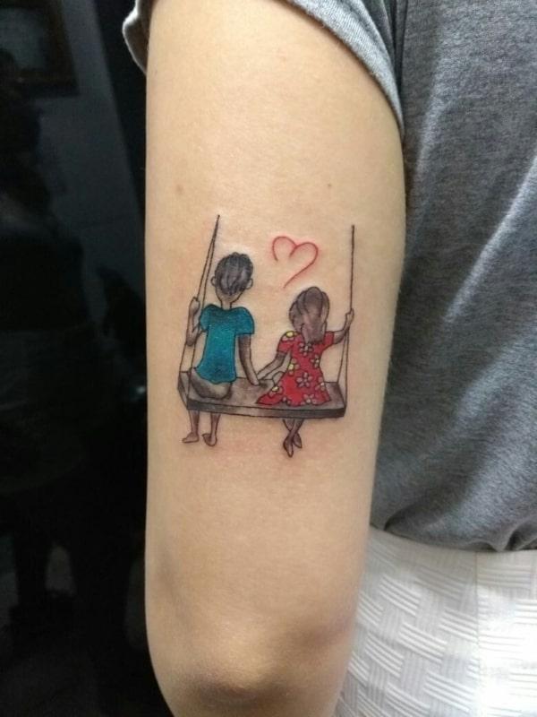 Tatuagem de bonequinhos para casal no braço
