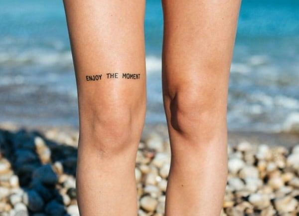 Tatuagem feminina no joelho escrita