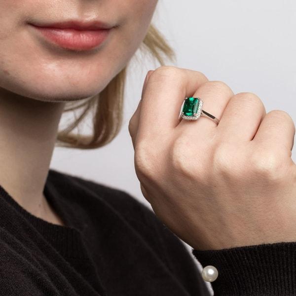 anel de ouro branco cravejado de diamantes e com pedra de esmeralda