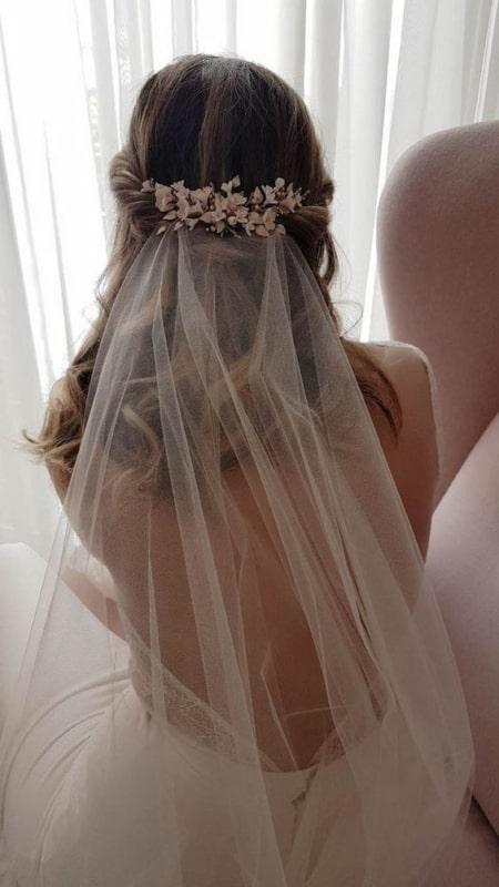 noiva com véu de tule e flores no cabelo
