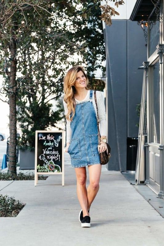 look de vestido jeans com blusa de frio e tênis