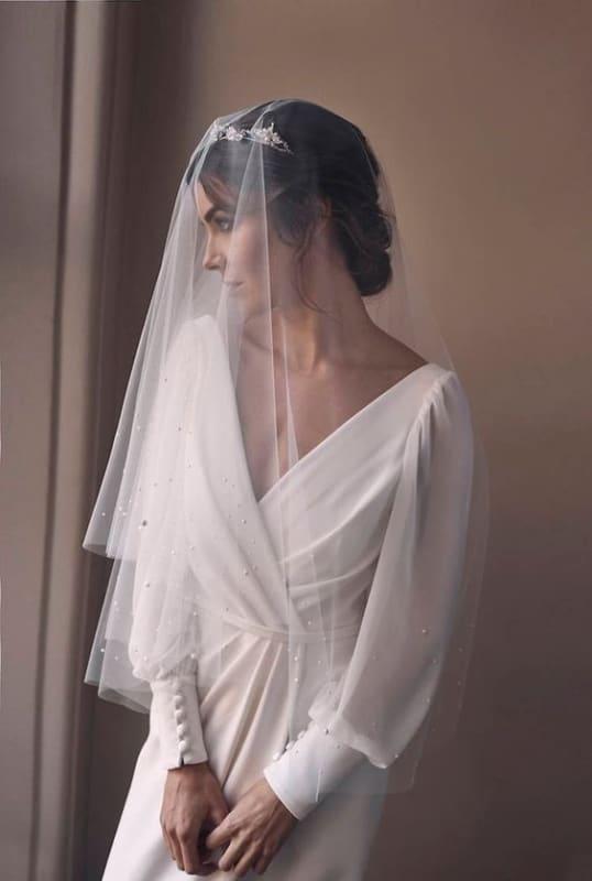noiva com penteado preso e véu bordado com pérolas