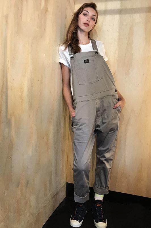 Jardineira cáqui com t shirt e tênis