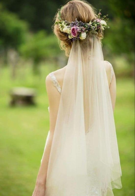 noiva com arranjo de flores e véu