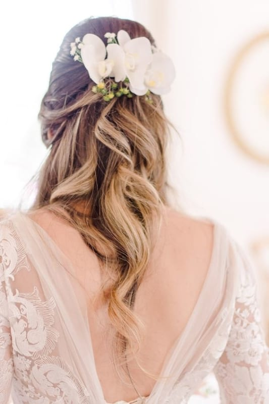noiva com penteado semi preso e arranjo de orquídeas brancas