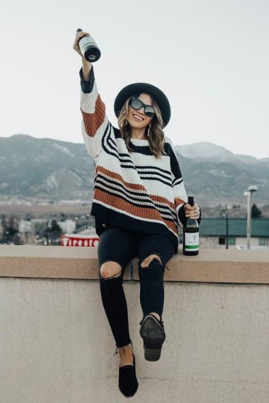 Calça preta destroyed com suéter de listras