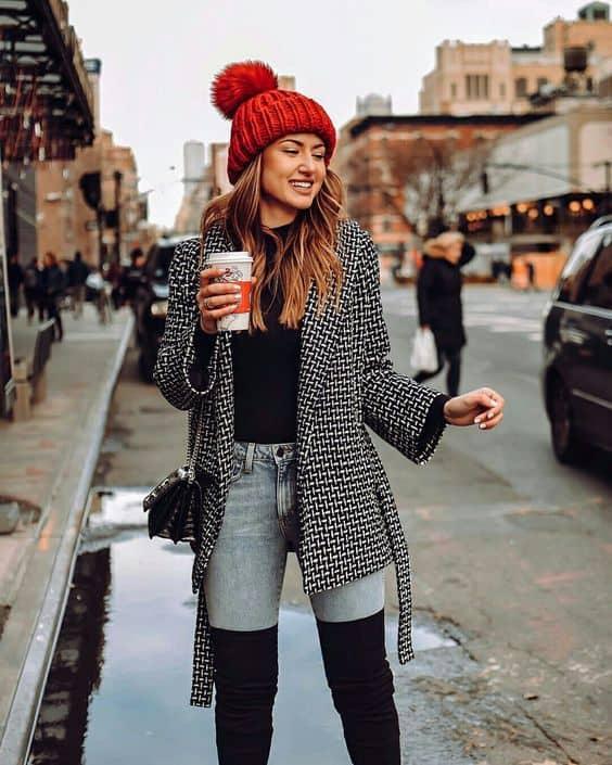 Look com casaco preto e branco e touca vermelha