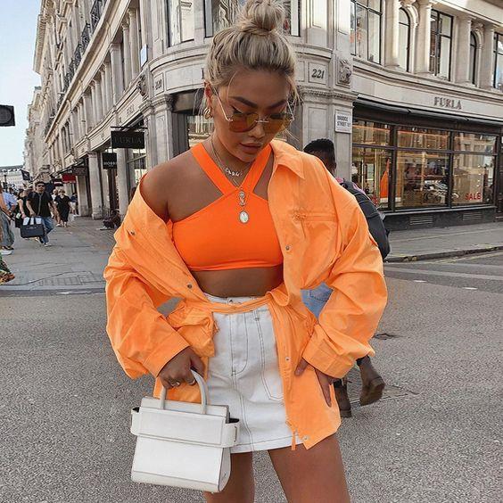 Look com cropped laranja neon e jaqueta
