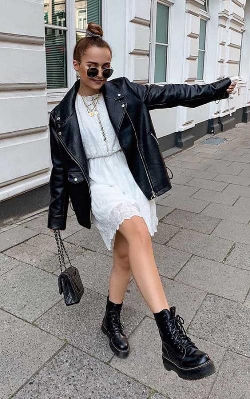 Look com vestido branco jaqueta de couro preta e bota de couro preta