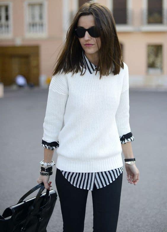 Look de inverno com suéter feminino branco e camisa listrada por baixo