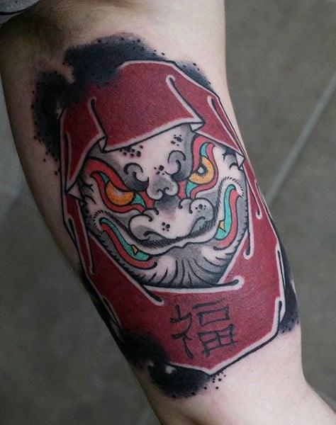 Tatuagem colorida masculina dragão daruma