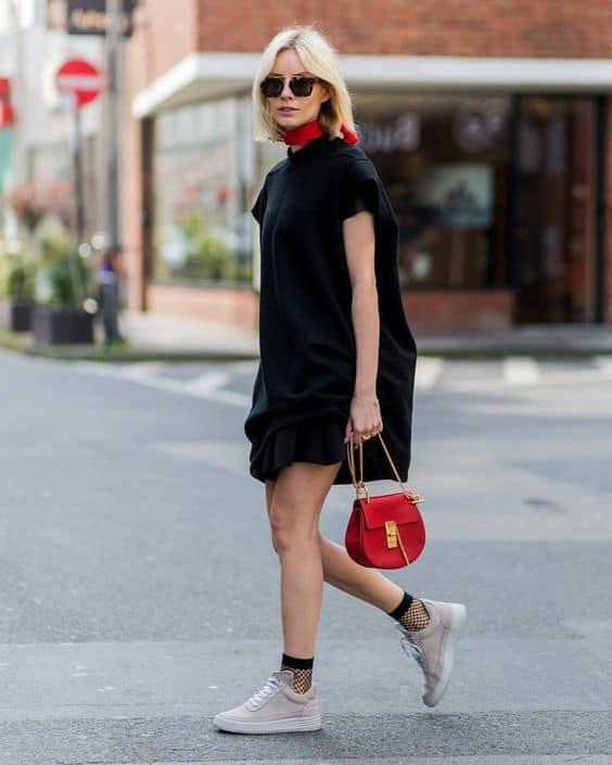 Vestido preto tênis casual e meia arrastão curta