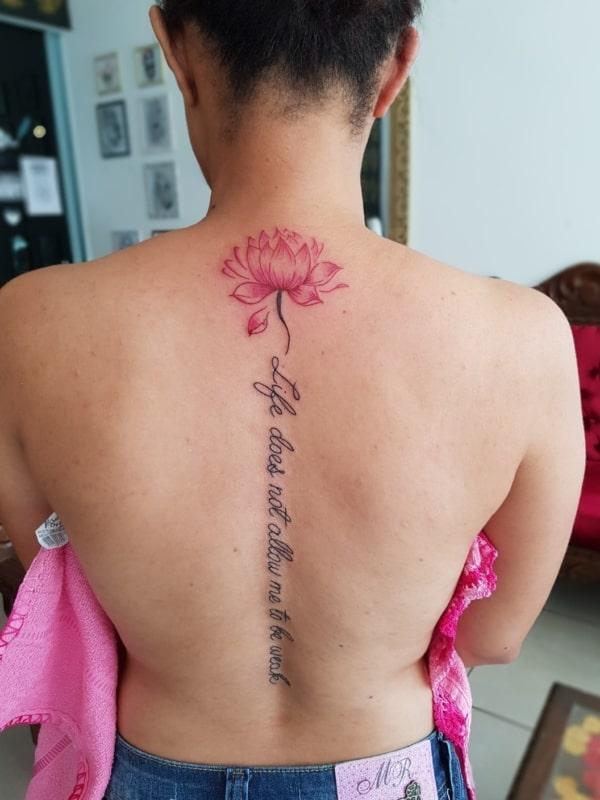 tatuagem na coluna com frase e flor
