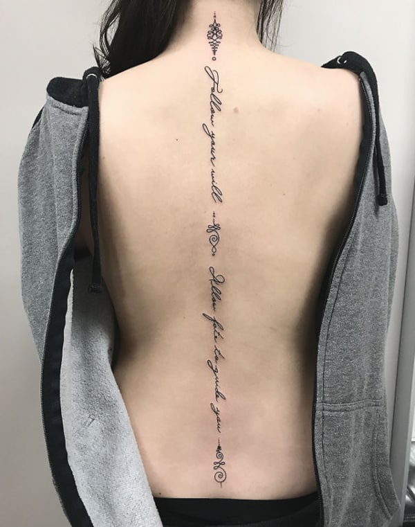 tatuagem na coluna com frase feminina