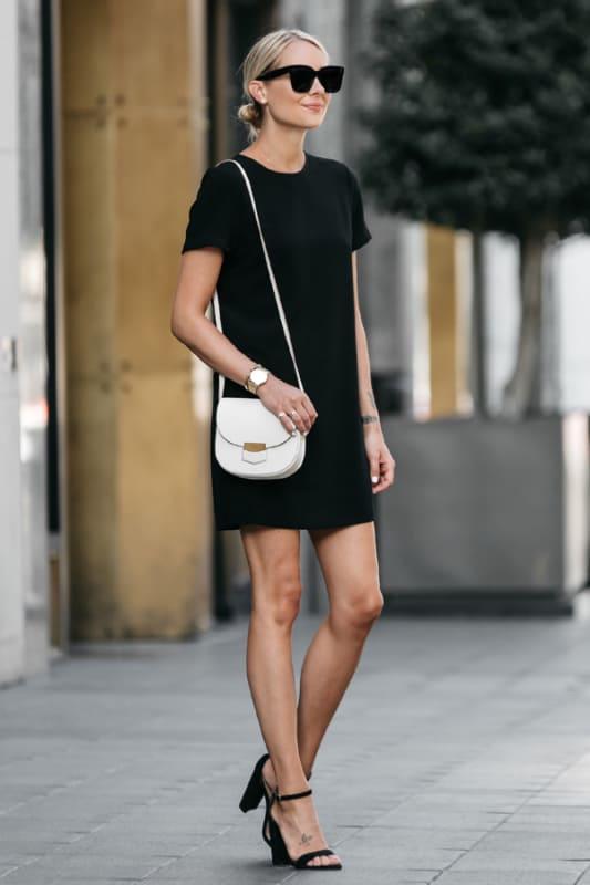 look com vestido preto e bolsa branca pequena