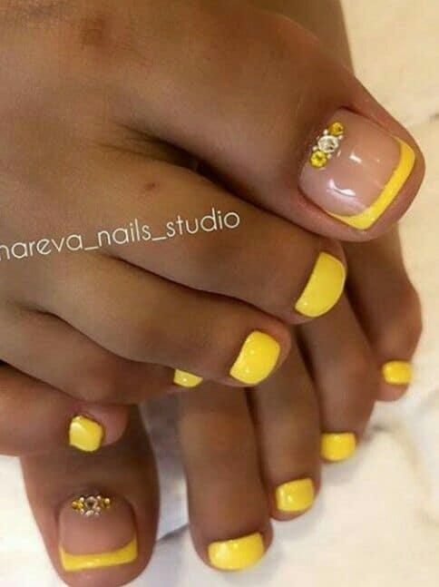 unha do pé decorada com esmalte amarelo