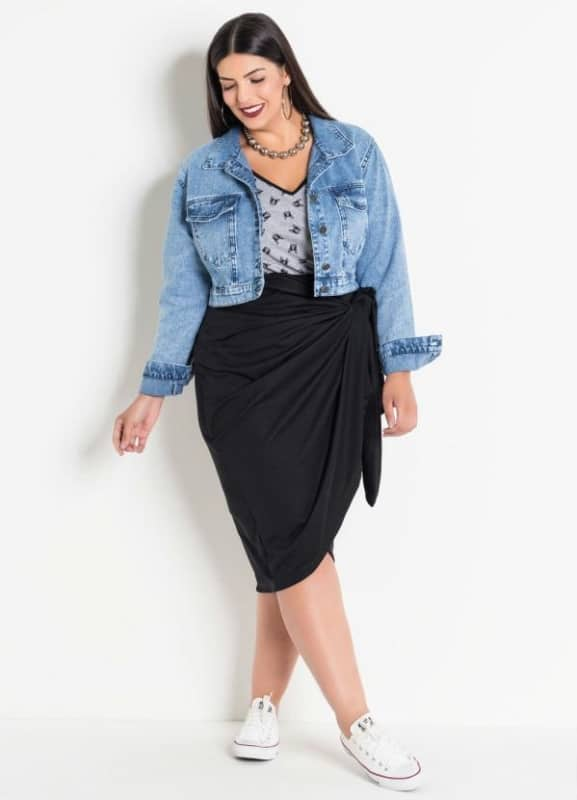look plus size com saia pareô preta e jaqueta jeans