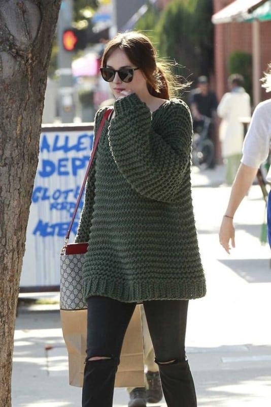 Dakota Johnson com pulôver verde escuro e calça destroyed preta