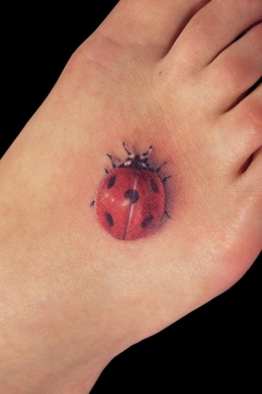 tatuagem de joaninha 3D no pé