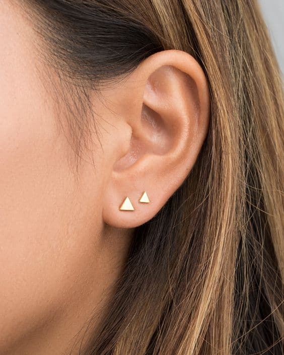furos no lobulo da orelha com brincos de triangulo