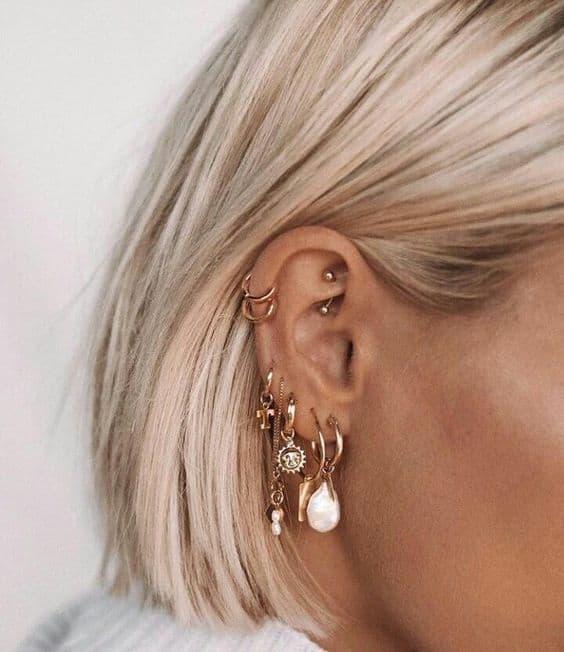orelha com varios furos e brincos dourados