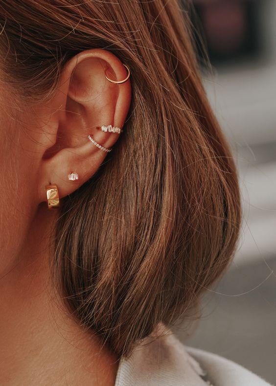 orelha com varios furos e brincos diferentes
