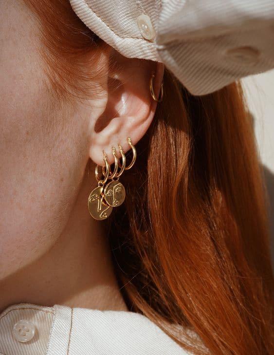 orelha furada com brincos de argolinhas com pingente