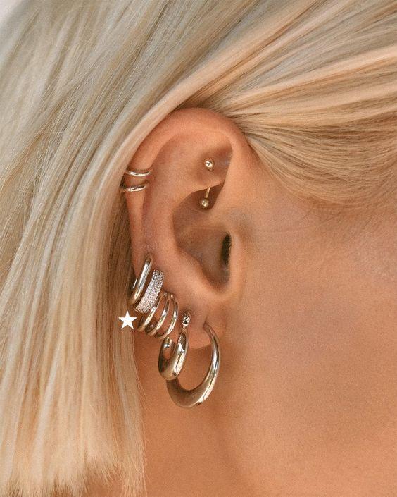 orelha com varios furos e brincos de argola diferentes