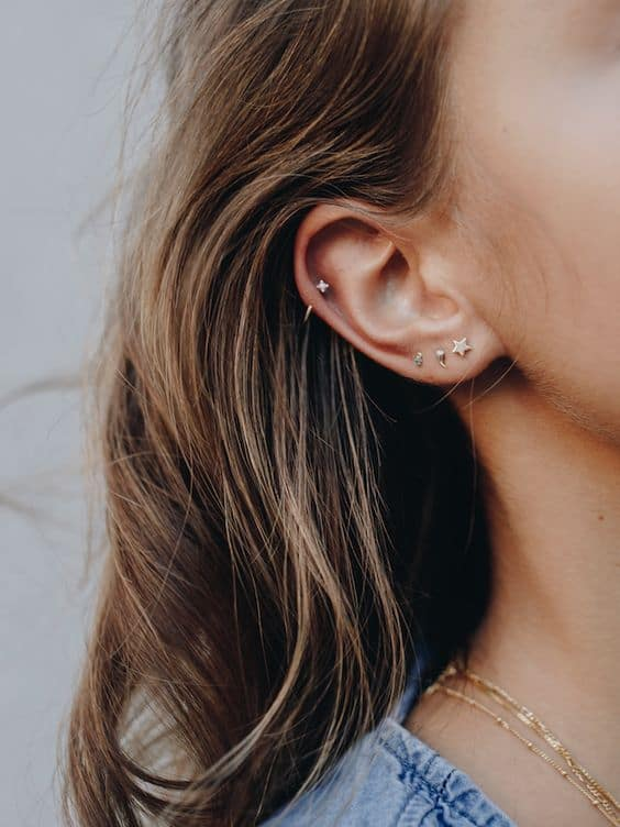 orelha com furos e brincos pequenos