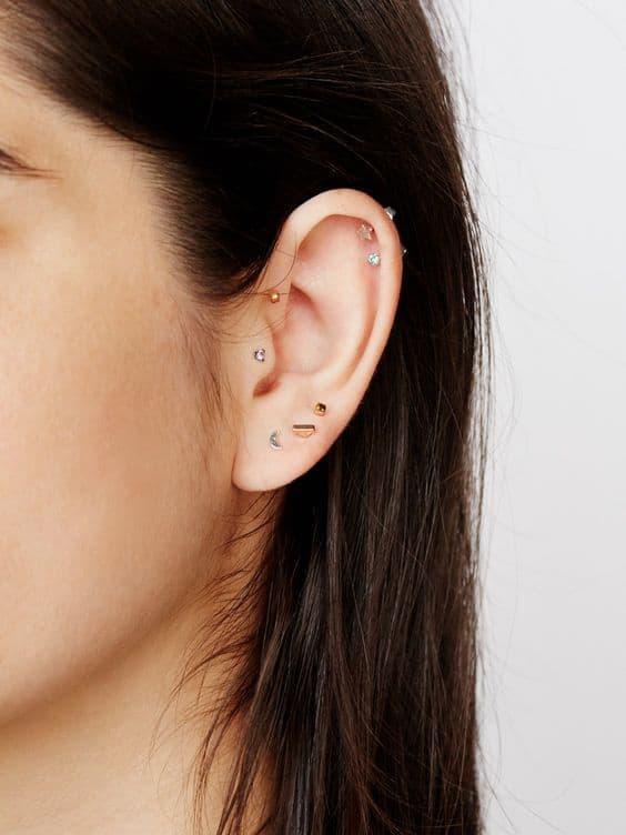 orelha com varios furos e brincos delicados
